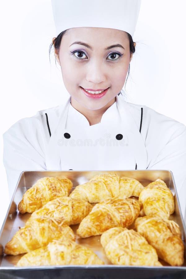O padeiro traz o croissant isolado no branco imagens de stock