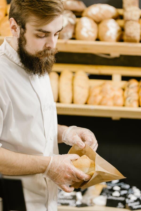 O padeiro carism?tico com uma barba e um bigode p?e o p?o fresco em um saco de papel na padaria imagens de stock royalty free