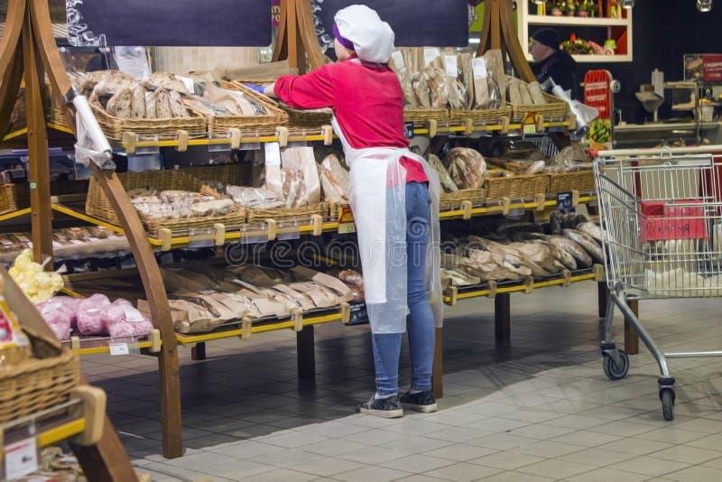 O padeiro da menina apresenta os bolos na janela da loja fotografia de stock
