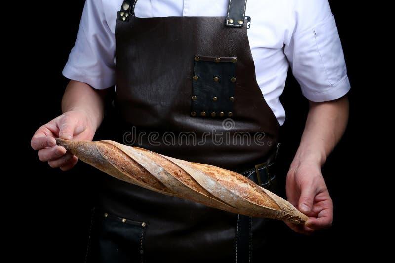 O padeiro mantém o baguette isolado no fundo preto fotos de stock royalty free