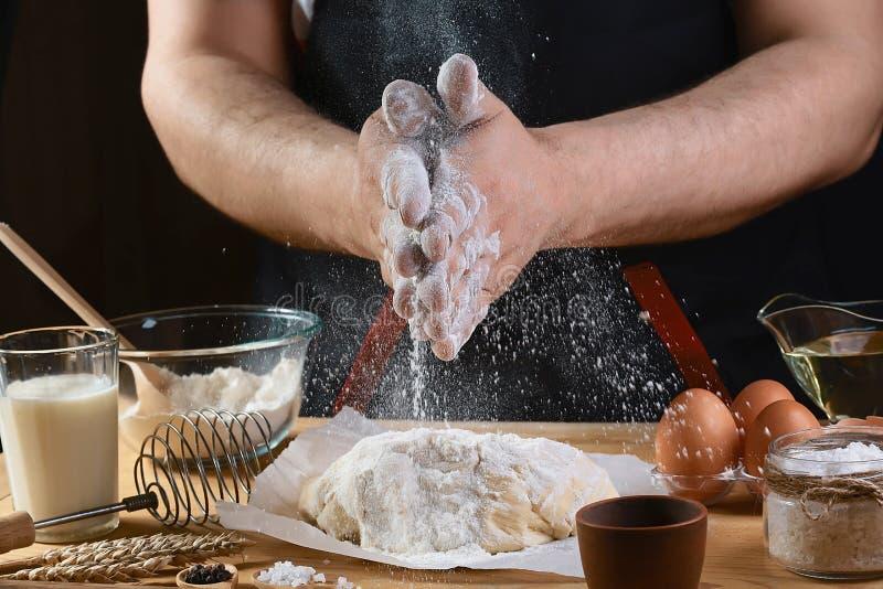 O padeiro polvilha a massa com os ingredientes da receita do pão, da pizza ou da torta da farinha com mãos, alimento no fundo da  fotos de stock royalty free