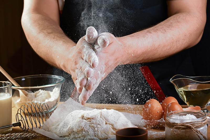 O padeiro polvilha a massa com os ingredientes da receita do pão, da pizza ou da torta da farinha com mãos, alimento no fundo da  foto de stock royalty free