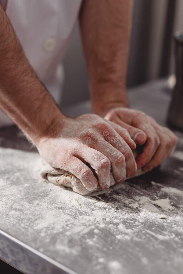 O padeiro profissional amassa a massa na tabela na cozinha da padaria fotos de stock royalty free