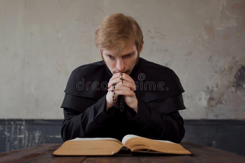 O padre leu a Bíblia Sacerdote católico novo considerável que reza ao deus imagens de stock