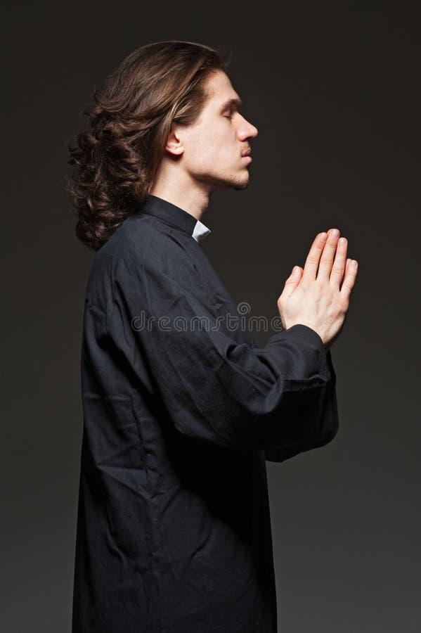 O padre novo praying de encontro ao fundo escuro imagem de stock