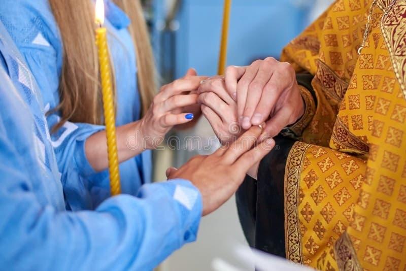 O padre põe as alianças de casamento sobre os dedos dos noivos na cerimônia de casamento na igreja imagem de stock royalty free