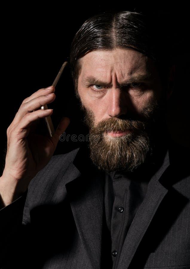 O padre superior do crente idoso com um smartphone, ancião farpado está chamando um fundo escuro imagens de stock royalty free