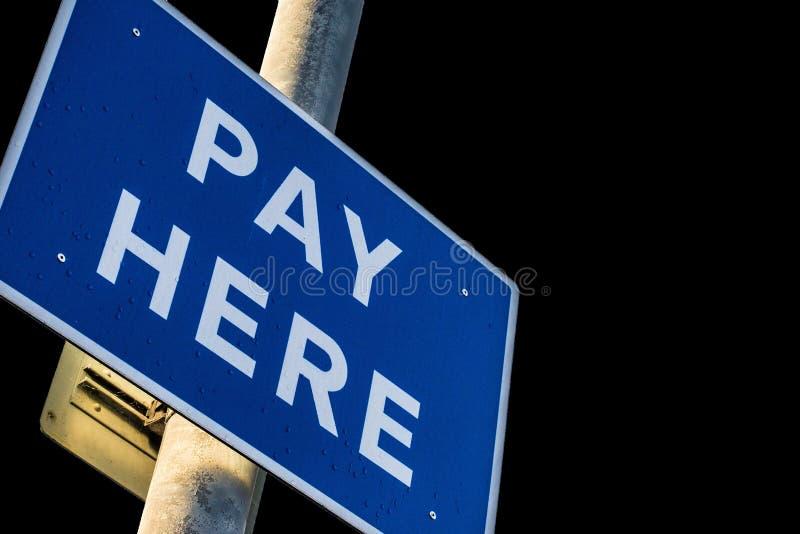 O pagamento do parque de estacionamento aqui assina em um Polo imagem de stock