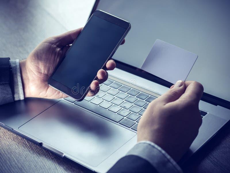 O pagamento em linha, ` s do homem entrega guardar um cartão de crédito e a utilização do telefone esperto para a compra em linha imagens de stock