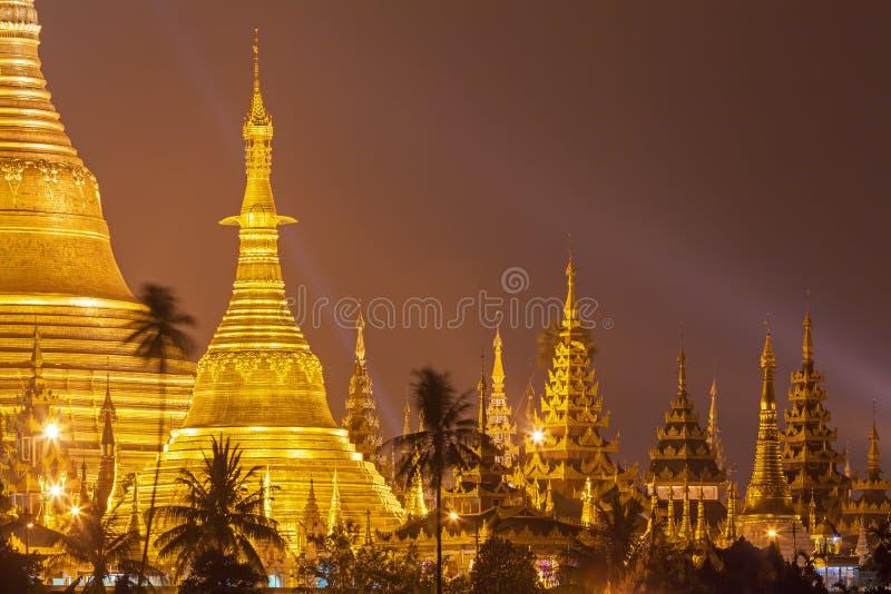 O pagode de Shwedagon na noite com projetor reflete a superfície do ouro do pagode foto de stock