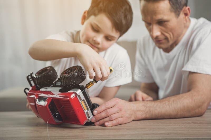 O pai é ensinando a filho como reparar o transporte do brinquedo fotos de stock