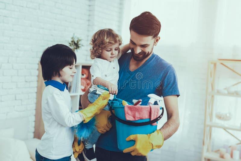 O pai é ensinar filhos uma limpeza fotos de stock