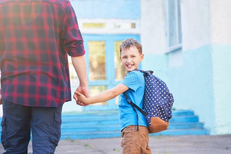 O pai acompanha a criança à escola um homem com uma criança removida da parte traseira paizinho doting que guarda a mão de seu fi foto de stock