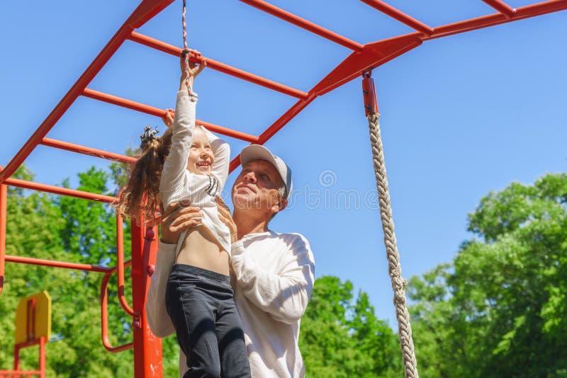 O pai ajuda a filha da sua criança a escalar a corda Conceito de ajudar jovens foto de stock