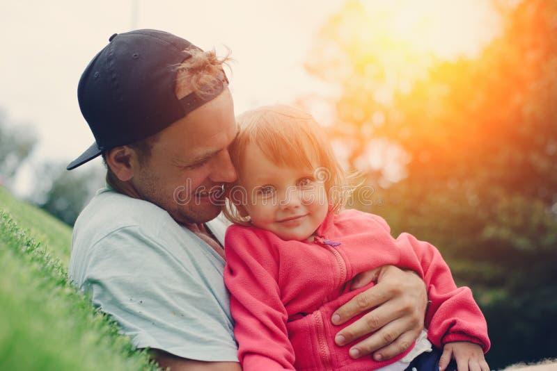 O pai alegre abraça a filha bonito e tempo do gasto no parque foto de stock royalty free