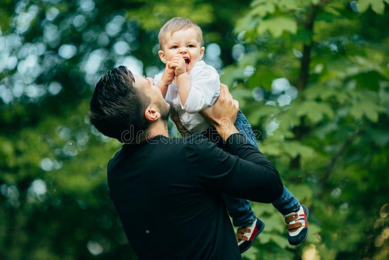 O pai alegre feliz que tem o divertimento joga acima no ar sua criança pequena foto de stock royalty free