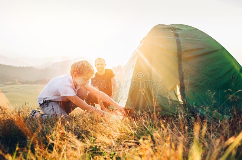 O pai aprende sua barraca de acampamento estabelecida filho na clareira da floresta do por do sol imagem de stock