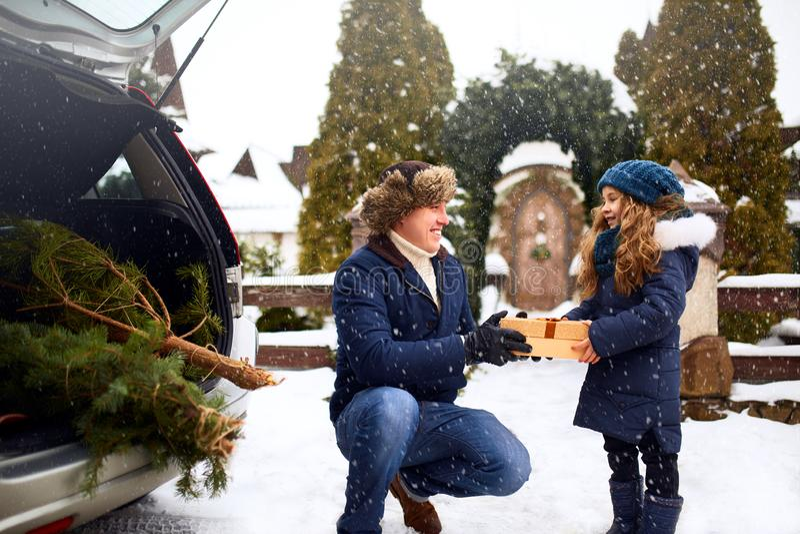 O pai apresenta a filha uma caixa de presente no dia de inverno nevado fora Árvore de Natal no grande tronco do carro de família  fotos de stock royalty free