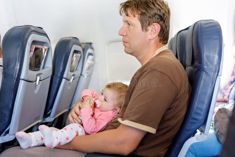 O pai cansado novo leva sua filha do bebê durante o voo no avião imagem de stock