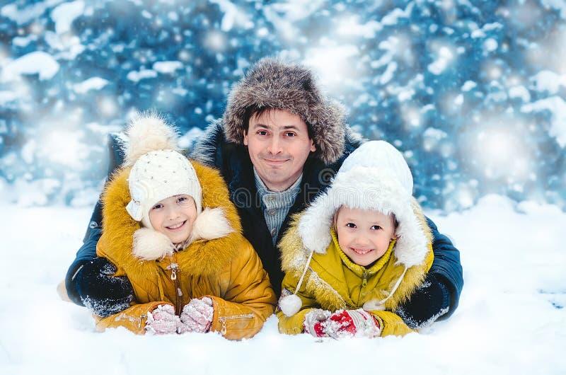 O pai com as crianças no sorriso de madeira do inverno fotografia de stock