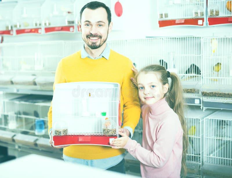 O pai com menina adquiriu a gaiola do canário e de pássaro foto de stock
