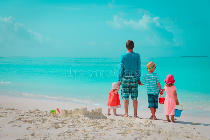 O pai com três crianças joga na praia, família no mar fotos de stock