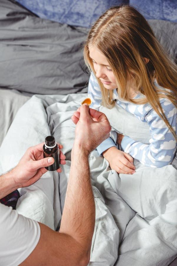O pai dá a medicina a seu doente fotografia de stock