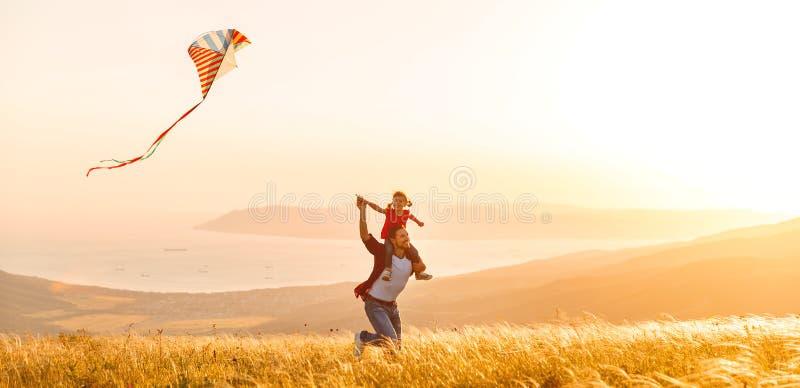 O pai da família e a filha felizes da criança correm com o papagaio no prado foto de stock