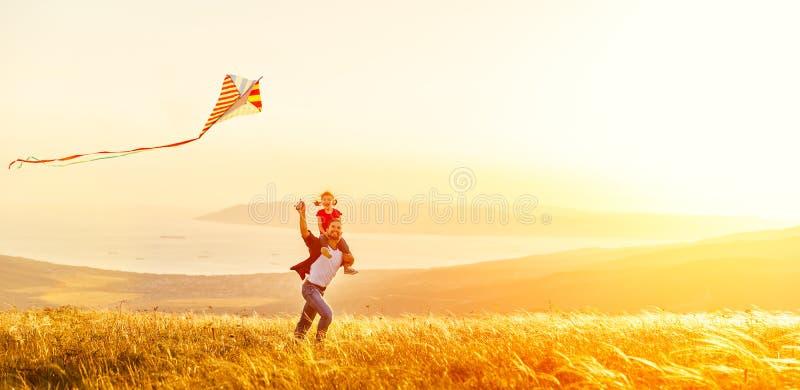 O pai da família e a filha felizes do bebê correm com o papagaio no prado fotografia de stock royalty free