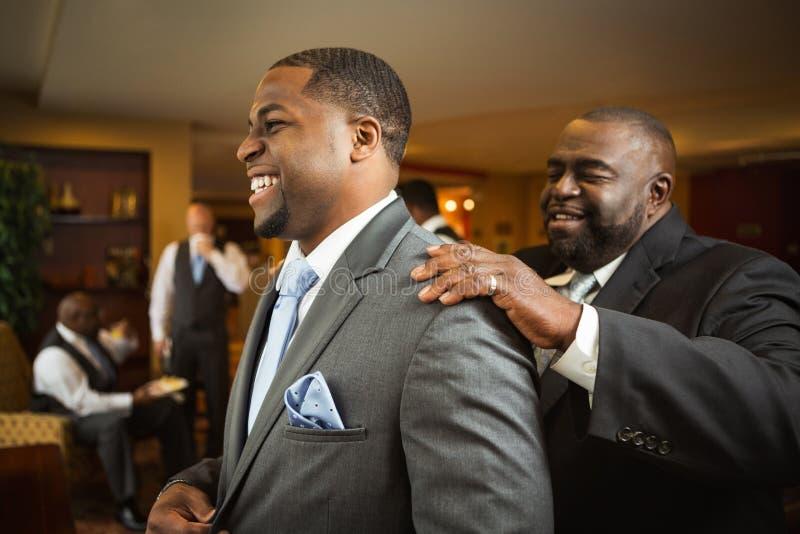 O pai do noivo que ajuda seu filho obtém vestido fotos de stock royalty free