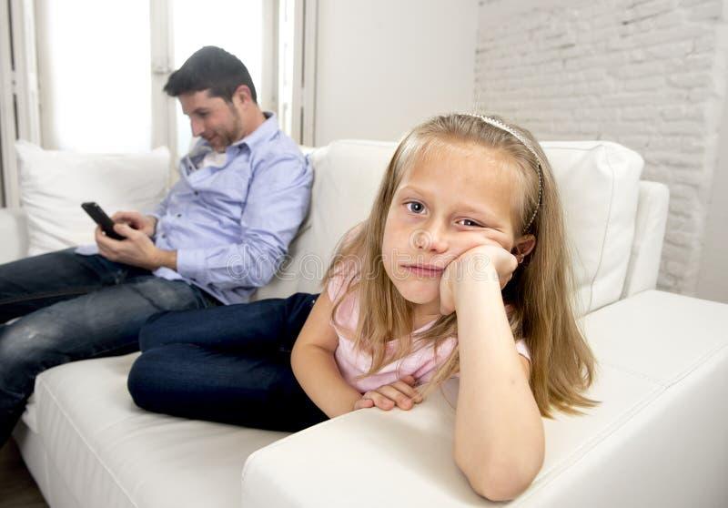 O pai do viciado do Internet que usa o telefone celular que ignora a filha triste pequena furou só e deprimido imagens de stock
