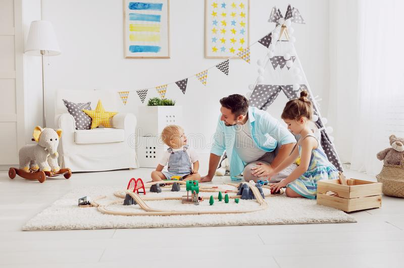O pai e as crianças da família jogam uma estrada de ferro do brinquedo na sala de jogos imagens de stock royalty free