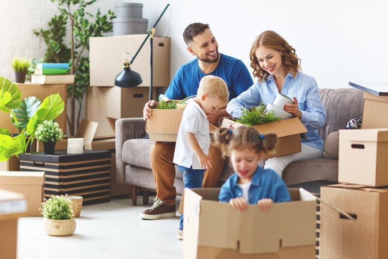 O pai e as crianças felizes da mãe da família transportam-se ao apartamento novo fotografia de stock royalty free