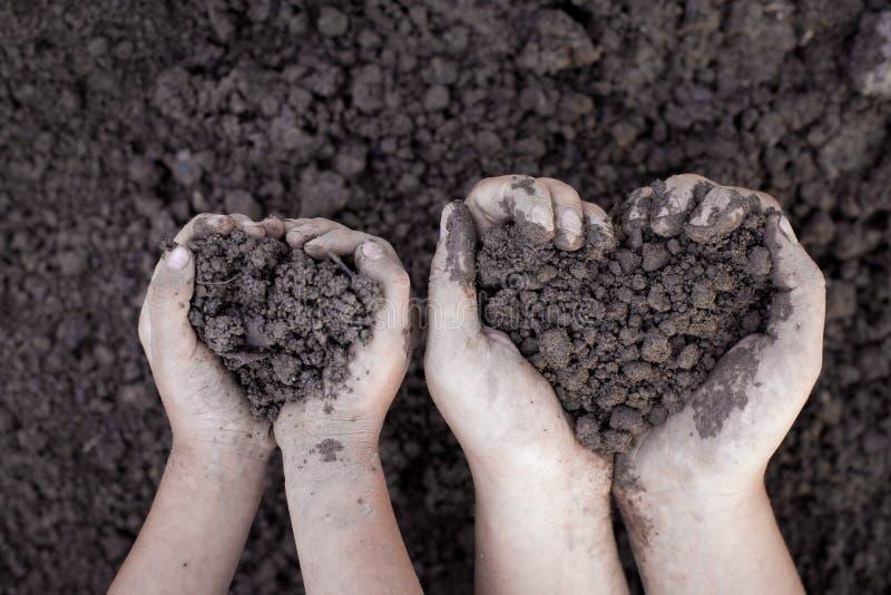 O pai e a criança entregam guardar o solo na forma do coração para plantar imagem de stock royalty free