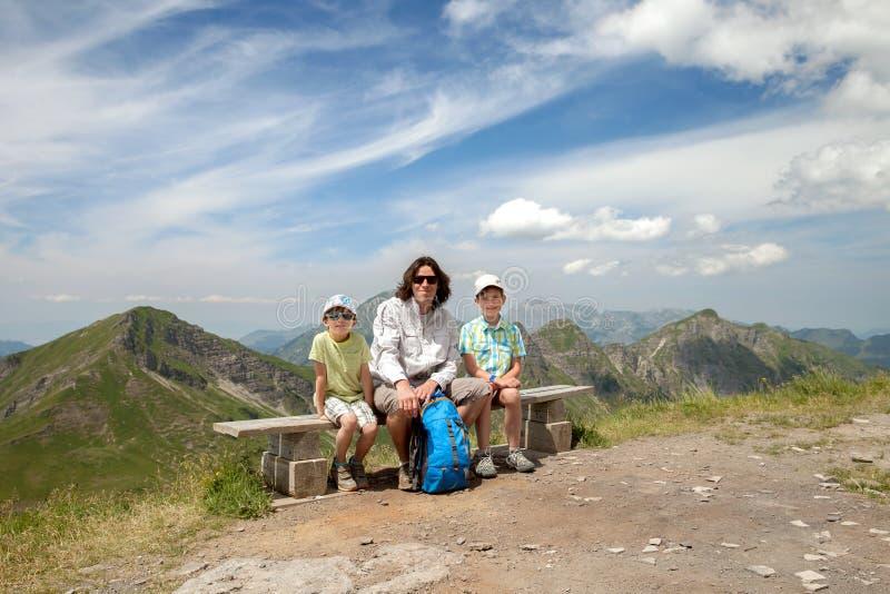 O pai e dois filhos estão sentando-se em um banco fotografia de stock royalty free