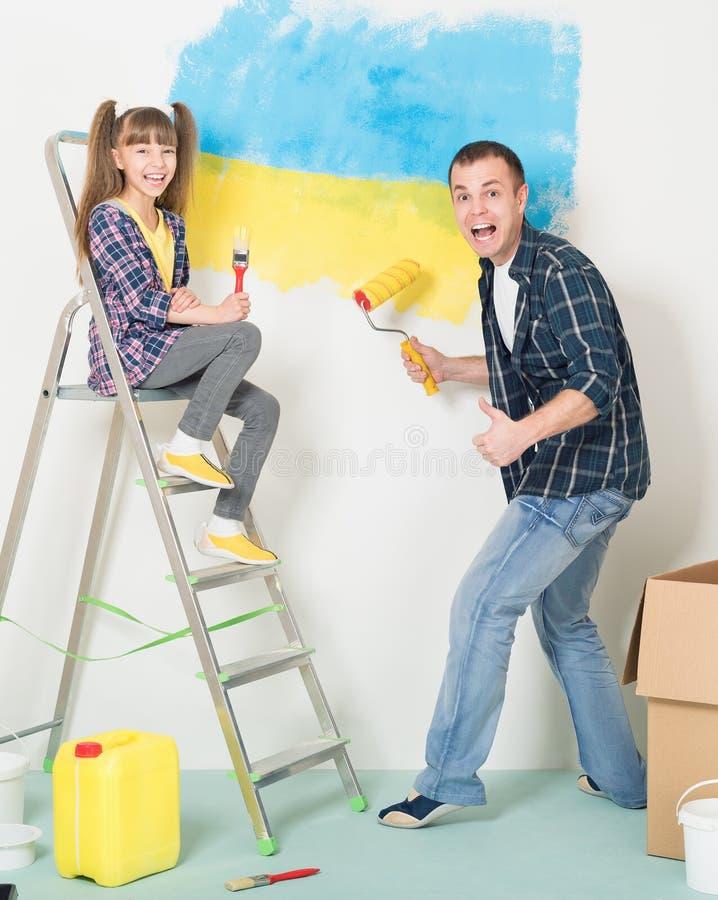 O pai e a filha fazem reparos em casa fotografia de stock royalty free