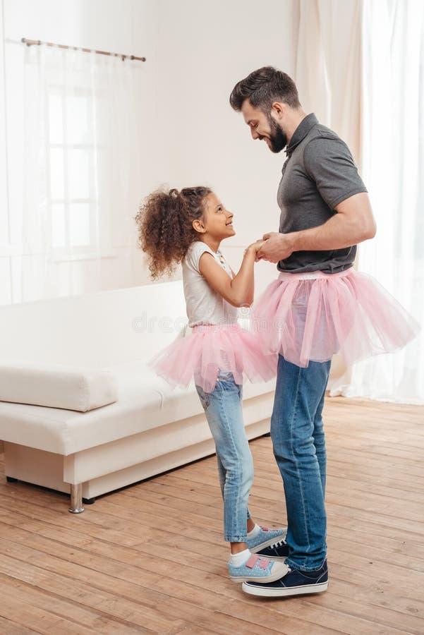 O pai e a filha no tule cor-de-rosa do tutu contornam a dança junto fotos de stock