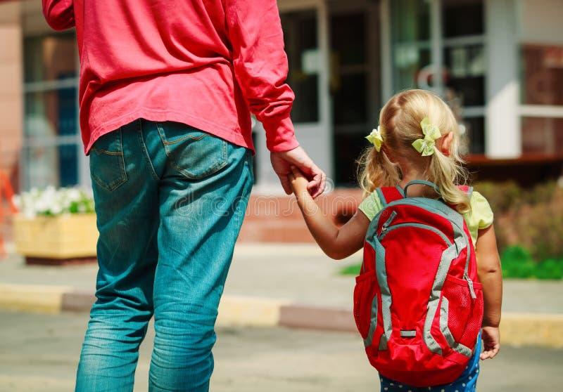 O pai e a filha pequena vão à escola ou à guarda imagem de stock
