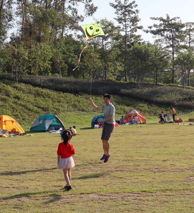 O pai e a filha, pessoa acamparam na grama no parque, verão em guangzhou, China foto de stock royalty free