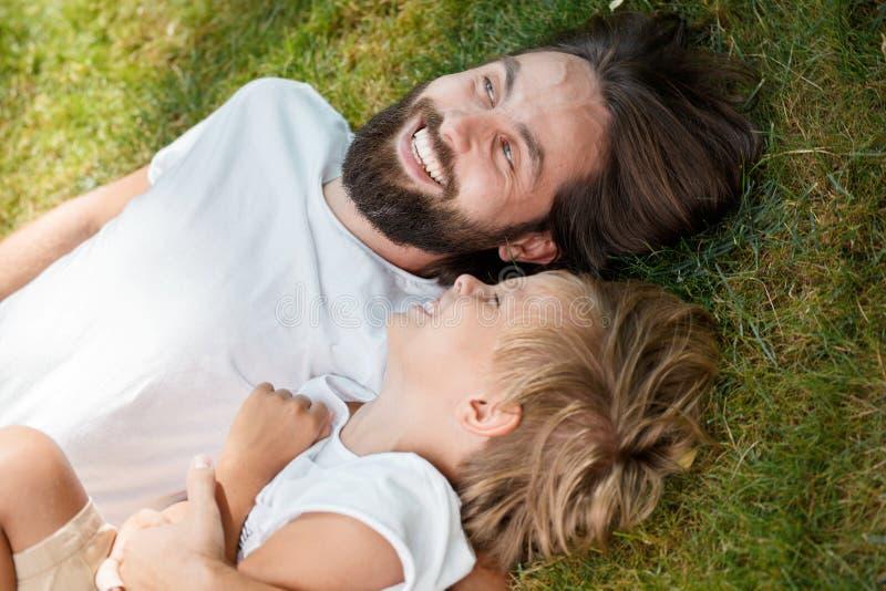 O pai e o filho alegres estão colocando junto na grama verde e estão rindo em um dia ensolarado foto de stock royalty free