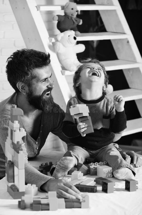 O pai e o filho com caras entusiasmado fazem construções coloridas com tijolos do brinquedo Família e conceito da infância Homem  fotografia de stock