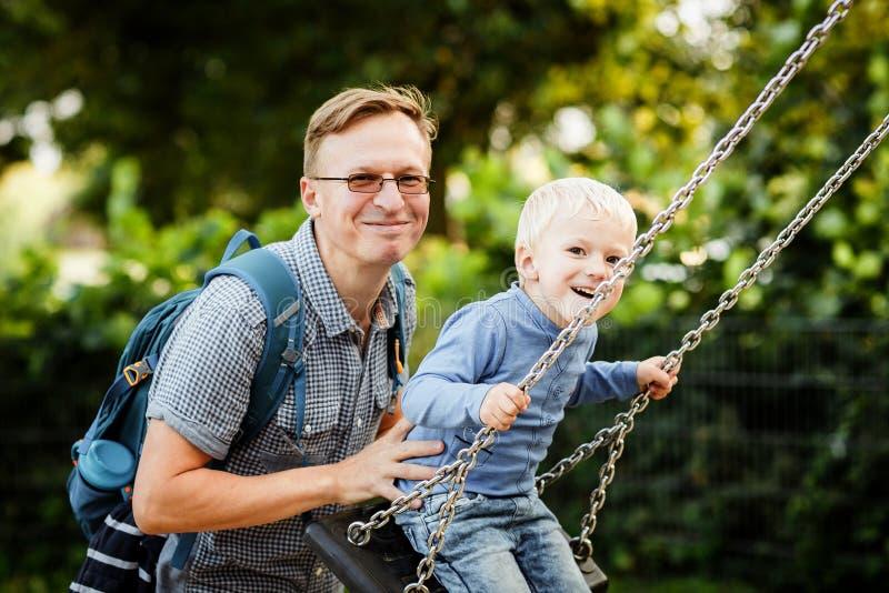 O pai e o filho estão balançando foto de stock