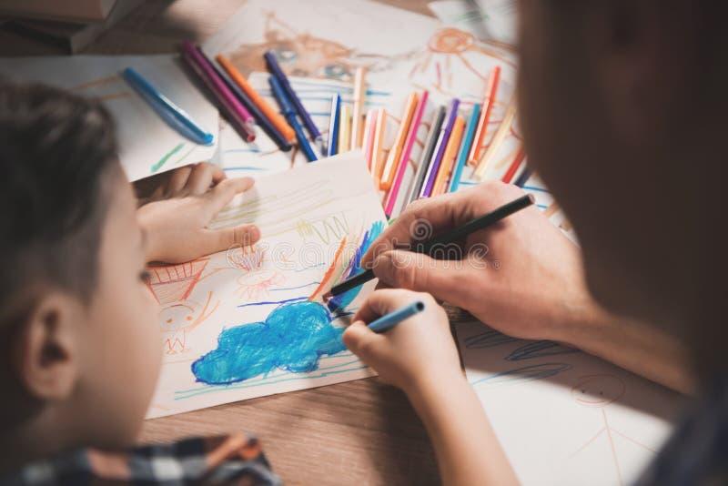 O pai e o filho estão tirando com lápis e marcadores da cor no papel na noite em casa imagens de stock royalty free