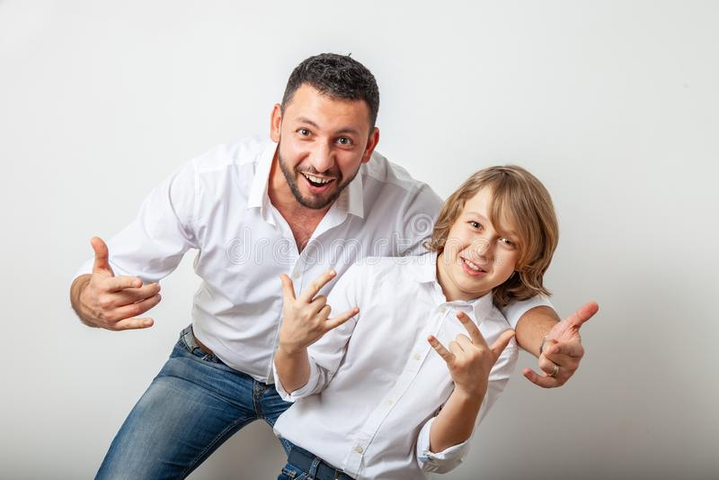 O pai e o filho fazem um gesto da cabra foto de stock