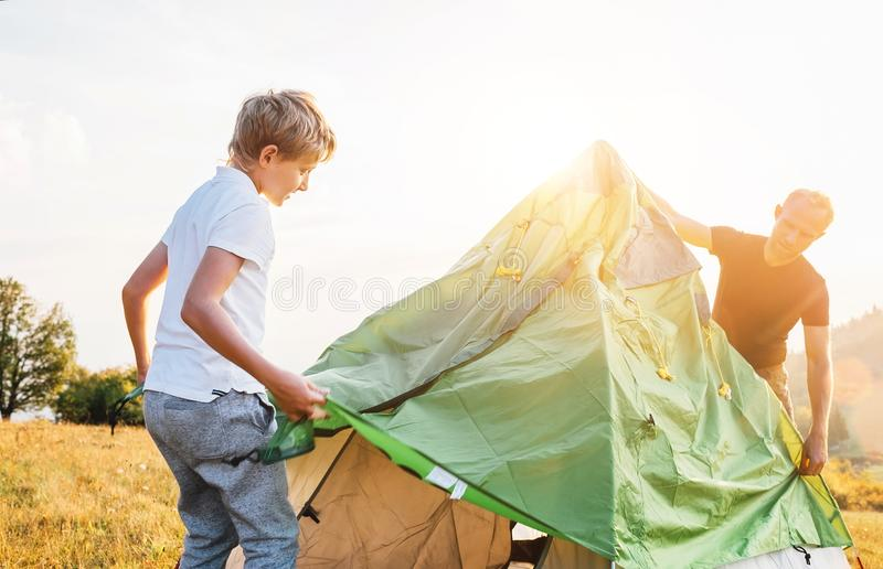 O pai e o filho instalam a barraca turística para acampar fotos de stock royalty free
