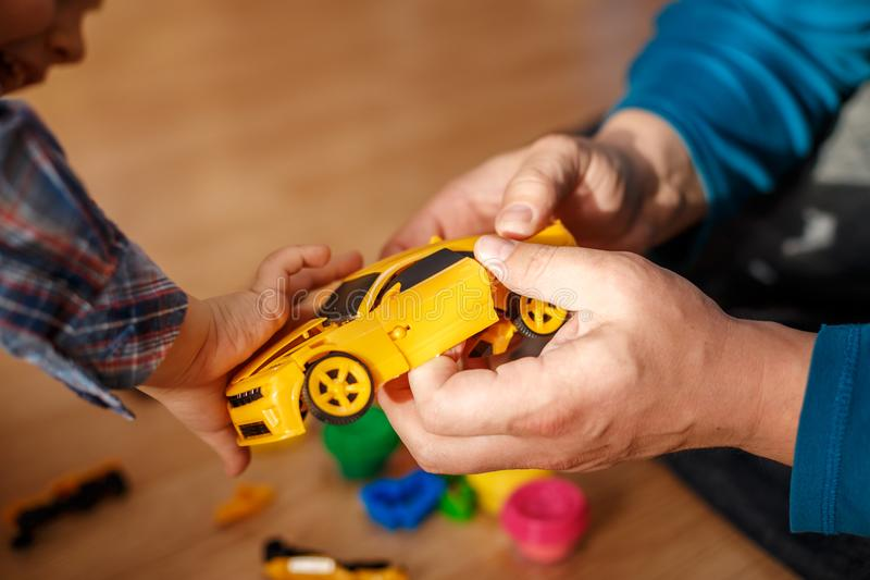 O pai e o filho jogam com lições das máquinas dos brinquedos com a criança imagens de stock royalty free
