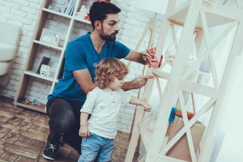 O pai e o filho limpam superfícies da mobília da poeira imagens de stock royalty free