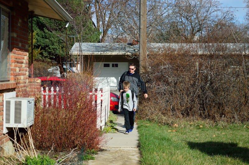 O pai e o filho obtêm a casa da escola imagem de stock