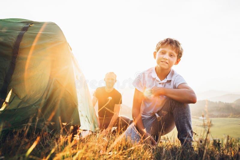 O pai e o filho preparam-se para o acampamento mountaing, estabelecem a barraca Trekking com imagem do conceito das crianças foto de stock royalty free