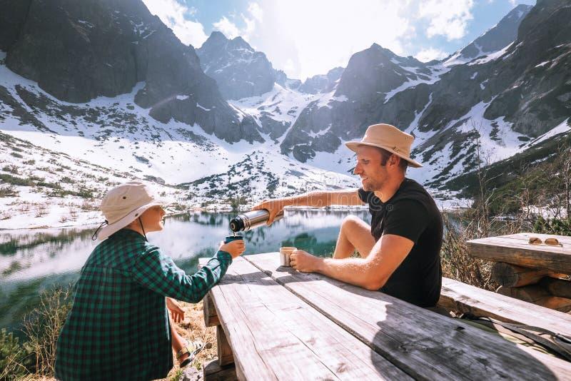 O pai e o filho que caminham o viajante descansam e bebem o chá perto da montagem fotografia de stock